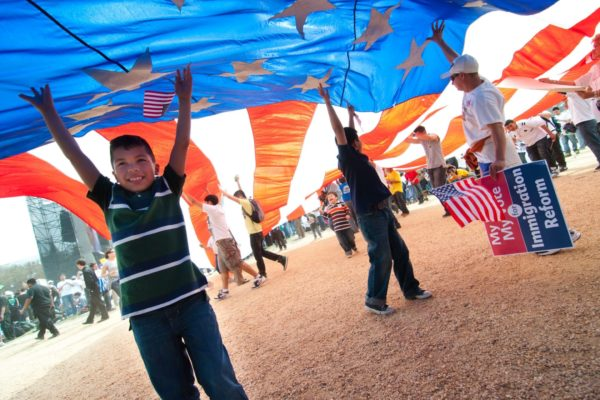 Young boy helping to hold a large American flag